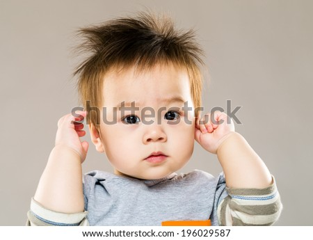 Sweet little boy with hand touch ear - stock photo