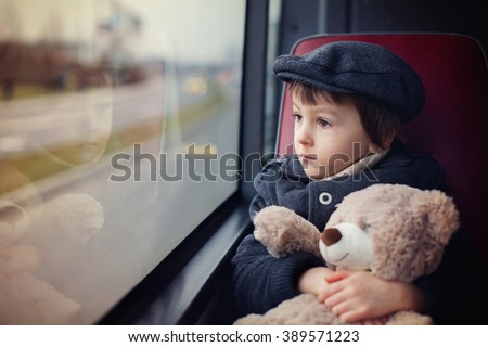 Sweet little child, preschool boy, riding in a bus, daytime, holding teddy bear - stock photo