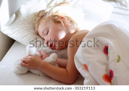 Sweet little child sleeping in bed. Healthy kid lying in bed. Blonde toddler girl resting in white sunny bedroom. - stock photo