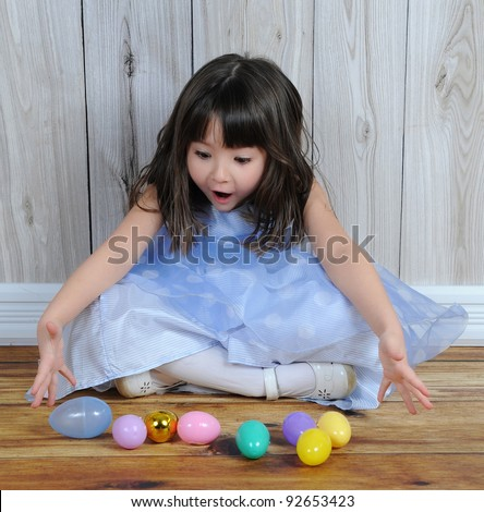sweet little girl excited over easter eggs in front of her - stock photo