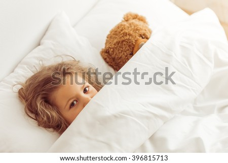 Sweet little girl is hiding with a teddy bear under her blanket while lying in bed at home - stock photo
