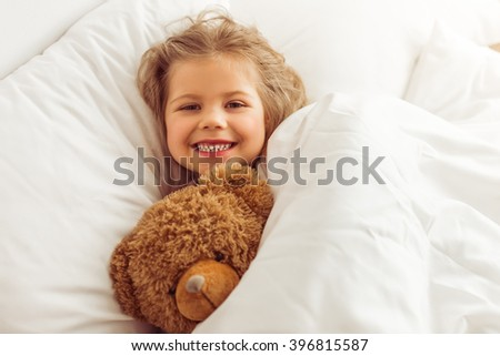 Sweet little girl is hugging a teddy bear, looking at camera and smiling while lying in her bed at home - stock photo