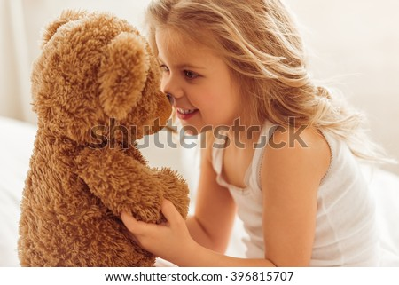 Sweet little girl is playing with a teddy bear and smiling while sitting on her bed at home - stock photo