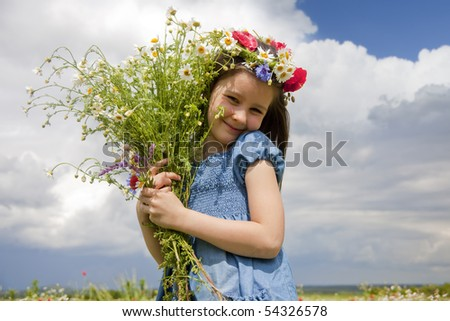 Sweet little girl on the field with summer flowers- poppies and daisies - stock photo