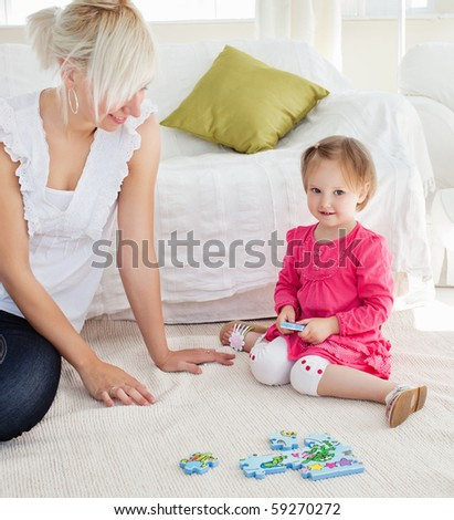 Sweet little girl playing with her mother in the living-room - stock photo