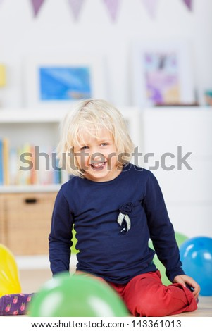 Sweet little girl playing with party balloons kneeling on the floor surrounded by colorful balloons grinning at the camera - stock photo