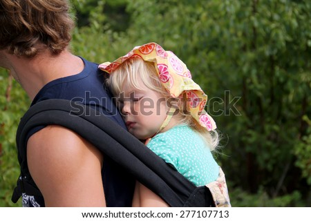 Sweet little girl slipping in the carrier on her father's back. Active family conception - stock photo
