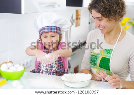 Sweet little girl sprinkle flour in kitchen - stock photo