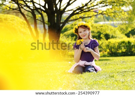 Sweet little girl with floral head wreath at the spring park, Moscow, Russia - stock photo