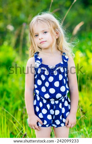 Sweet little girl with long blond curly hair, outdoor full length portrait in summer park on bright sunny day. Thoughtful child in green grass field. Calmness and tenderness. - stock photo