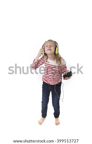 sweet little girl 7 years old with blonde hair and closed eyes listening to music with headphones and mobile phone singing and dancing happy and excited  isolated on white background - stock photo
