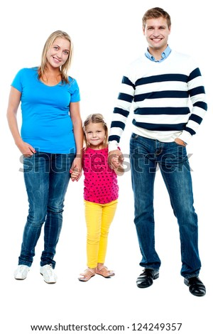 Sweet little kid standing in between her parents and holding their hands. Full length portrait - stock photo