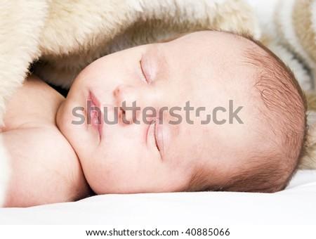Sweet little sleeping baby cozy in a blanket - stock photo