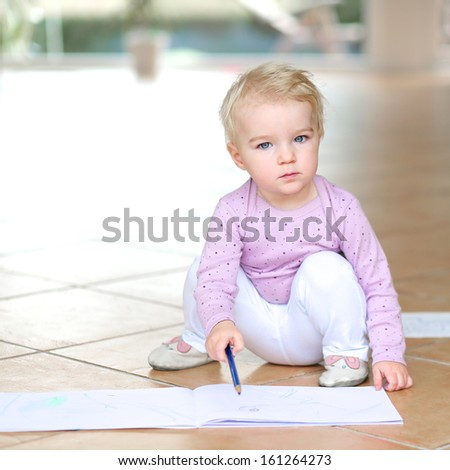 Sweet lovely baby girl plays indoors drawing with colorful pencils sitting on tiles floor - stock photo