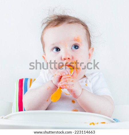 Sweet messy baby eating a carrot in a white high chair - stock photo