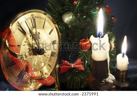 Sweet New year`s Night composition with golden clock, candles and decorated christmas tree - stock photo
