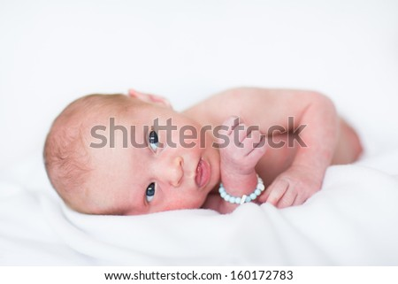 Sweet newborn baby boy relaxing on a white blanket - stock photo