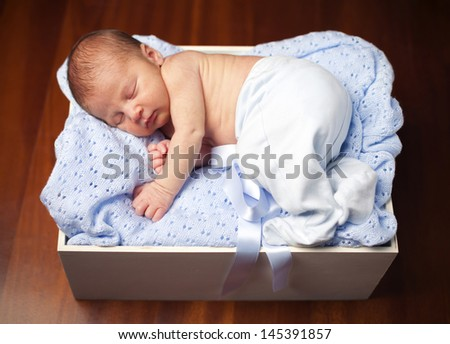 Sweet newborn baby sleeping in a wooden box - stock photo