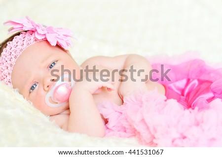 sweet newborn girl is wearing tutu skirt - stock photo