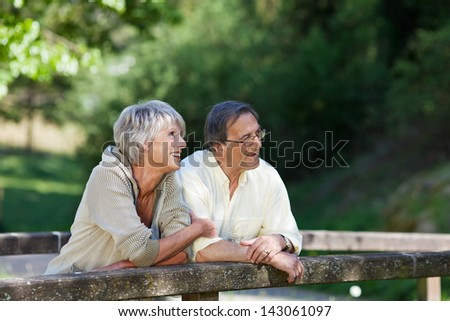 Sweet old couple having a conversation and relaxing while standing on the bridge inside the park. - stock photo