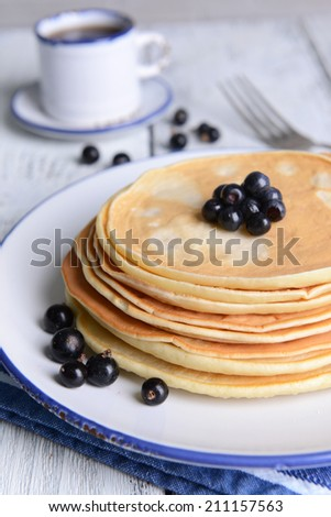 Sweet pancakes with berries on table close-up - stock photo