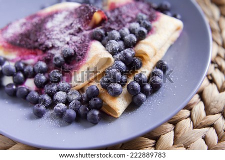 Sweet pancakes with cheese, blueberries, cream and sugar. Shown on the gray plate, a background pad withdrawals from natural grass and wicker. Food ingredients are flour, summer,milk, egg, cheese - stock photo