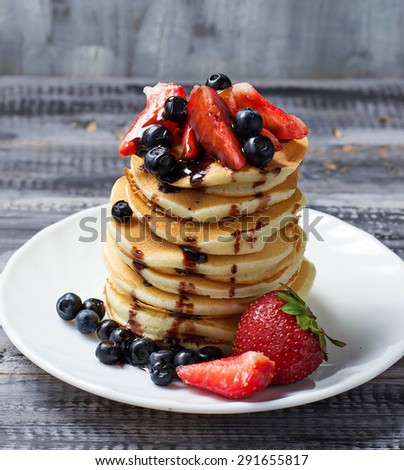 Sweet pancakes with fresh berries. Selective focus - stock photo