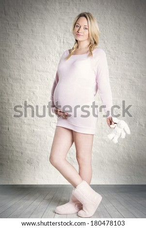 Sweet picture of beautiful pregnant woman in cozy dress standing embrace her belly and holds toy rabbit in hands. - stock photo