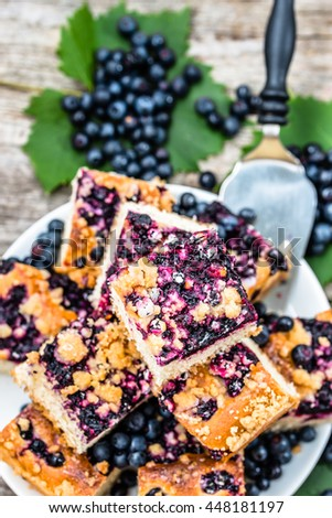 Sweet pie with blueberry fruits on yeast pastry, summer baking concept from above - stock photo