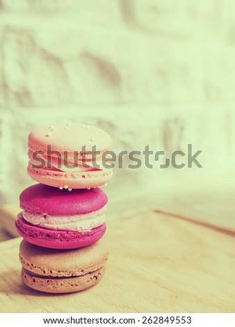 Sweet pink and brown macarons or macaroons on wooden plate with white wall in vintage style. For copy space. - stock photo