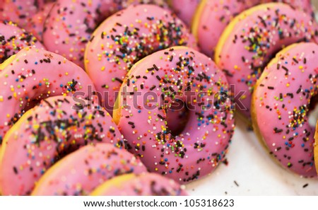 Sweet pink fresh donuts at shop counters - stock photo
