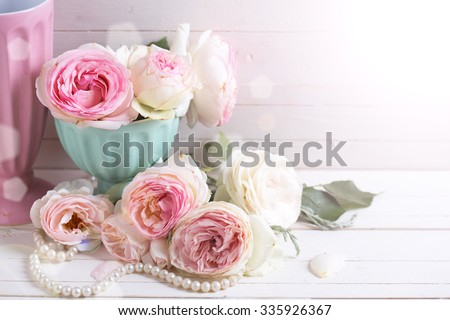 Sweet pink roses flowers in vase  in ray of light on white painted wooden background.  Selective focus. Place for text.  - stock photo