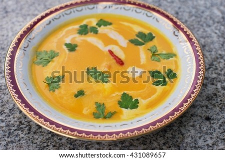 Sweet potato creamy soup asian or thai style vegan soup prepared from sweet potatoes or yam with chili, curry, coconut milk, ginger, onion and fresh leaves of coriander. Fresh and spicy healthy food. - stock photo