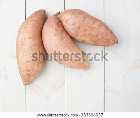 Sweet potato or Ipomoea batatas composition over the white wooden boards surface - stock photo