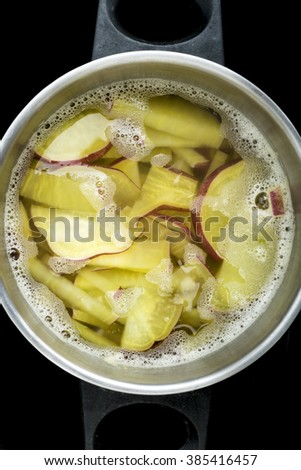 Sweet Potatoes boiled in pot on stove isolated on black background - stock photo