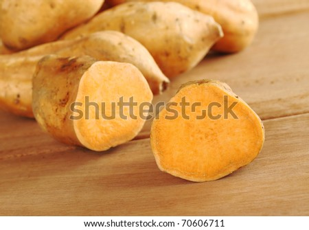Sweet potatoes halves (lat. Ipomoea batatas) on wooden surface (Selective Focus, Focus on the half in the front) - stock photo