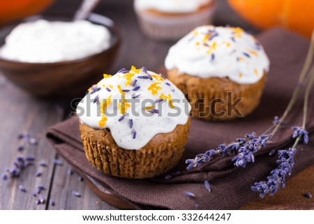 Sweet pumpkin cupcake with cream cheese icing decorated with lavender, selective focus - stock photo