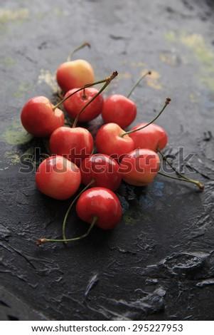 Sweet Rainier cherries on an old painted tray - stock photo
