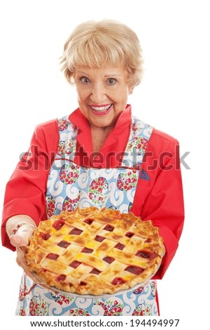 Sweet retro style grandmother holding a delicious home baked cherry pie with lattice top crust.  Isolated on white.   - stock photo