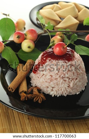 Sweet rice with strawberry sauce, anise and cinnamon - stock photo