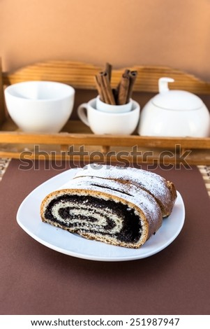 Sweet roll with poppy seeds on the plate - stock photo