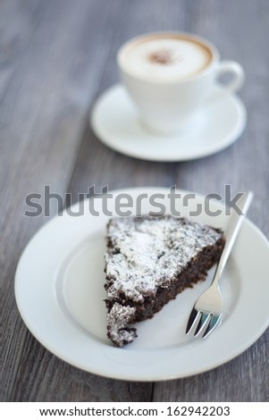 Sweet slice of brownie served with espresso doppio. Homemade dessert decorated with sugar powder. - stock photo