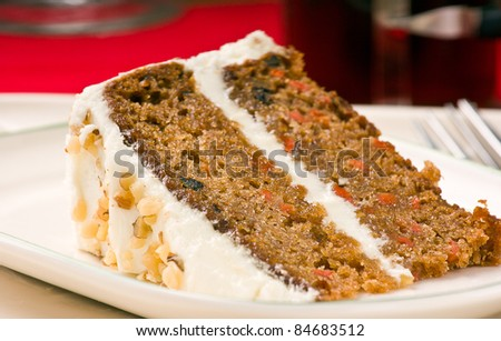 Sweet slice of walnut carrot cake on white plate. Shallow depth of field. - stock photo
