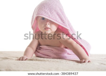 Sweet small baby covered with a rose towel with big eyes - stock photo