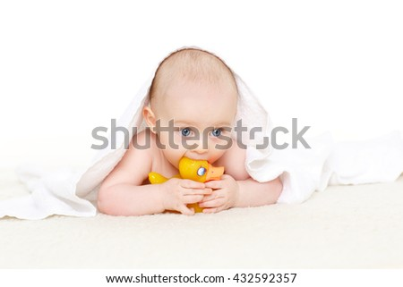 Sweet small baby covered with a towel, lies on a plaid on a white background.Cute infant after bath. 5 months old. - stock photo