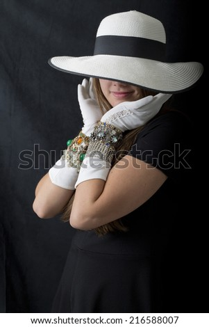 Sweet smile on this young woman's face half covered with big floppy hat brim and framed with white gloved hands. - stock photo