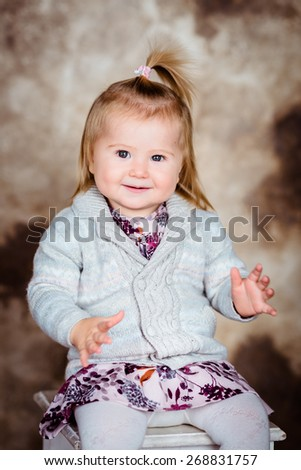 Sweet smiling little girl with blond hair sitting on chair and clapping her hands. Studio portrait on brown grunge background - stock photo