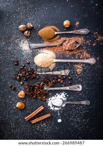Sweet spices in the spoons on the table a black background - stock photo