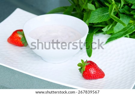 Sweet strawberry berries served with fresh organic yoghurt in a white bowl on a table. Fresh fruit dessert for the breakfast served with a mint bunch. Selective focus, copy space - stock photo