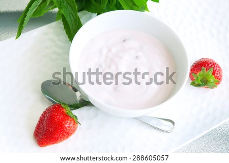 Sweet strawberry berries served with fresh organic yogurt in a white bowl on a table. Fresh fruit dessert for the breakfast served with a mint bunch. Selective focus, copy space - stock photo